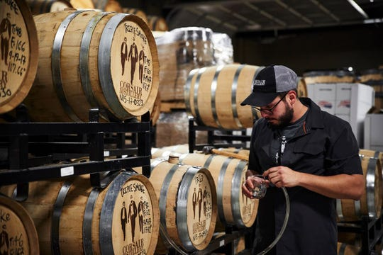 Corsair Barrel House Manager Adrian Thompson pulls samples from barrels for distillers to taste and determine which are ready to decant.