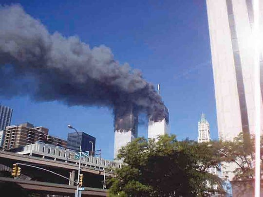 This photo of the twin towers in New York City burning on the morning on Sept. 11, 2001, was taken by Fairview resident Cindy New, who was sightseeing in Battery Park with her future husband John New.