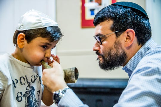 Rabbi Fishel Zaklos teaches Jude Rubenstein, 4, how to blow a shofar, which is sounded for Rosh Hashana, at the Chabad Naples Jewish Community Center on Wednesday, Sept. 5, 2018.