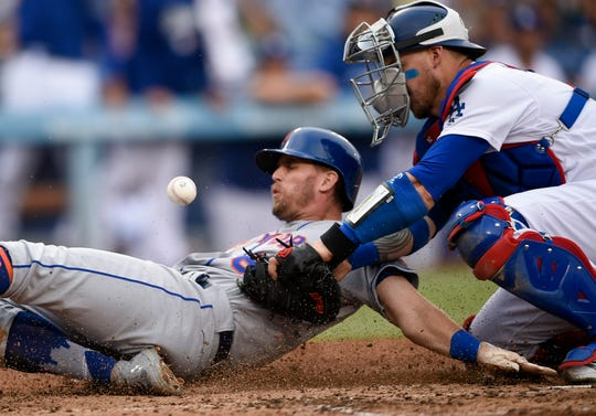 New York Mets second baseman Jeff McNeil (68) slides to home as Los Angeles Dodgers catcher Yasmani Grandal (9) misses a pass at home plate during the fourth inning at Dodger Stadium.