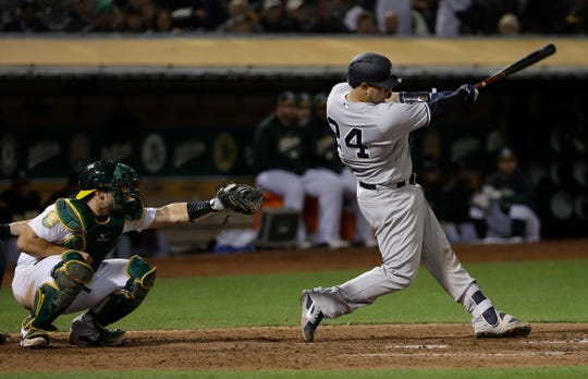 New York Yankees' Gary Sanchez, right, hits a two-run home run in front of Oakland Athletics catcher Josh Phegley during the seventh inning of a baseball game in Oakland, Calif., Wednesday, Sept. 5, 2018.