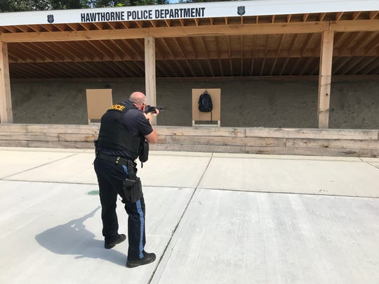 Hawthorne Police Sgt. James W. Geier aims his Benelli M2 Tactical 12-guage shotgun at a bulletproof backpack.