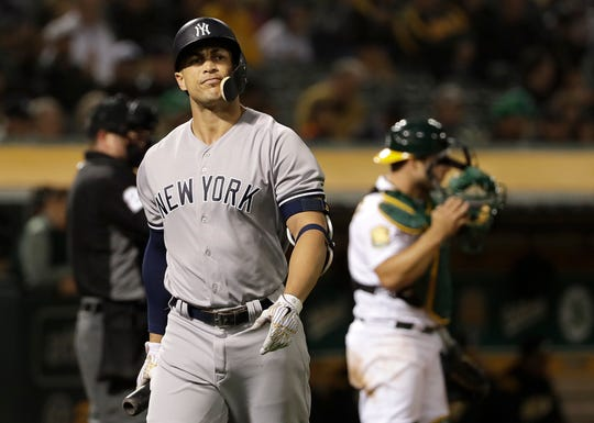 New York Yankees' Giancarlo Stanton, left, walks toward the dugout after striking out against the Oakland Athletics during the sixth inning of a baseball game in Oakland, Calif., Wednesday, Sept. 5, 2018. At right is Athletics catcher Josh Phegley.