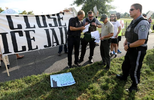 Rev. Seth Kaper-Dale, shows park police his permit to hold a protest.  Kaper-Dale led approximately two dozen people at a protest against Hudson County's contract with ICE.  They chose to protest at Liberty State Park in Jersey City due to the fact New Jersey Democrats were holding a fundraiser across the street at the time. Thursday, September 6, 2018