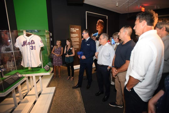 """Former NY Mets players John Franco (2nd from R) and Todd Zeile (R), two leaders of the 2001 team with the New York City Fire Commissioner Daniel Nigro (4th from R), as they are guided on a tour by Clifford Chanin (3rd from R), Executive Vice President and Deputy Director for Museum Programs at the new special exhibition """"Comeback Season: Sports After 9-11"""" at the 9-11 Museum in New York on 09/06/18."""