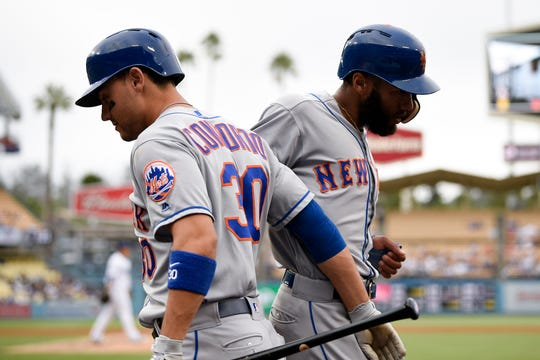 New York Mets shortstop Amed Rosario (1) celebrates with left fielder Michael Conforto (30) after running in a score during the fourth inning against the Los Angeles Dodgers at Dodger Stadium.