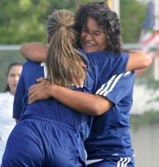 Lady 'Cats Daniela Aguirre (facing) and senior Mireya Trujillo embrace after Trujillo's second-half goal sent the match into sudden-death overtime.