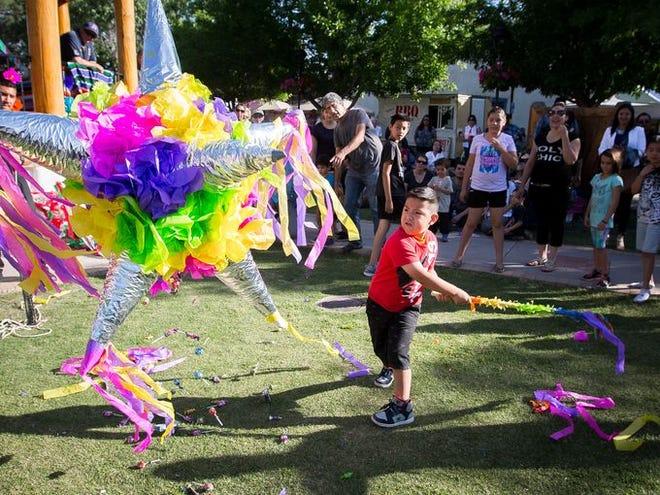 A young boy takes a swing at a piñata at the Diez y Seis de Septiembre Fiesta in Mesilla.