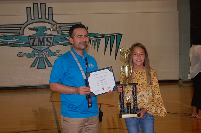 Zia Middle School seventh-grader Emily Lilley is presented with a trophy and certificate by Principal Joel Aguilar after winning first place among all New Mexico students in the InvestWrite essay writing contest. Competing as a sixth-grader, Lilley won the spring 2018 competition.