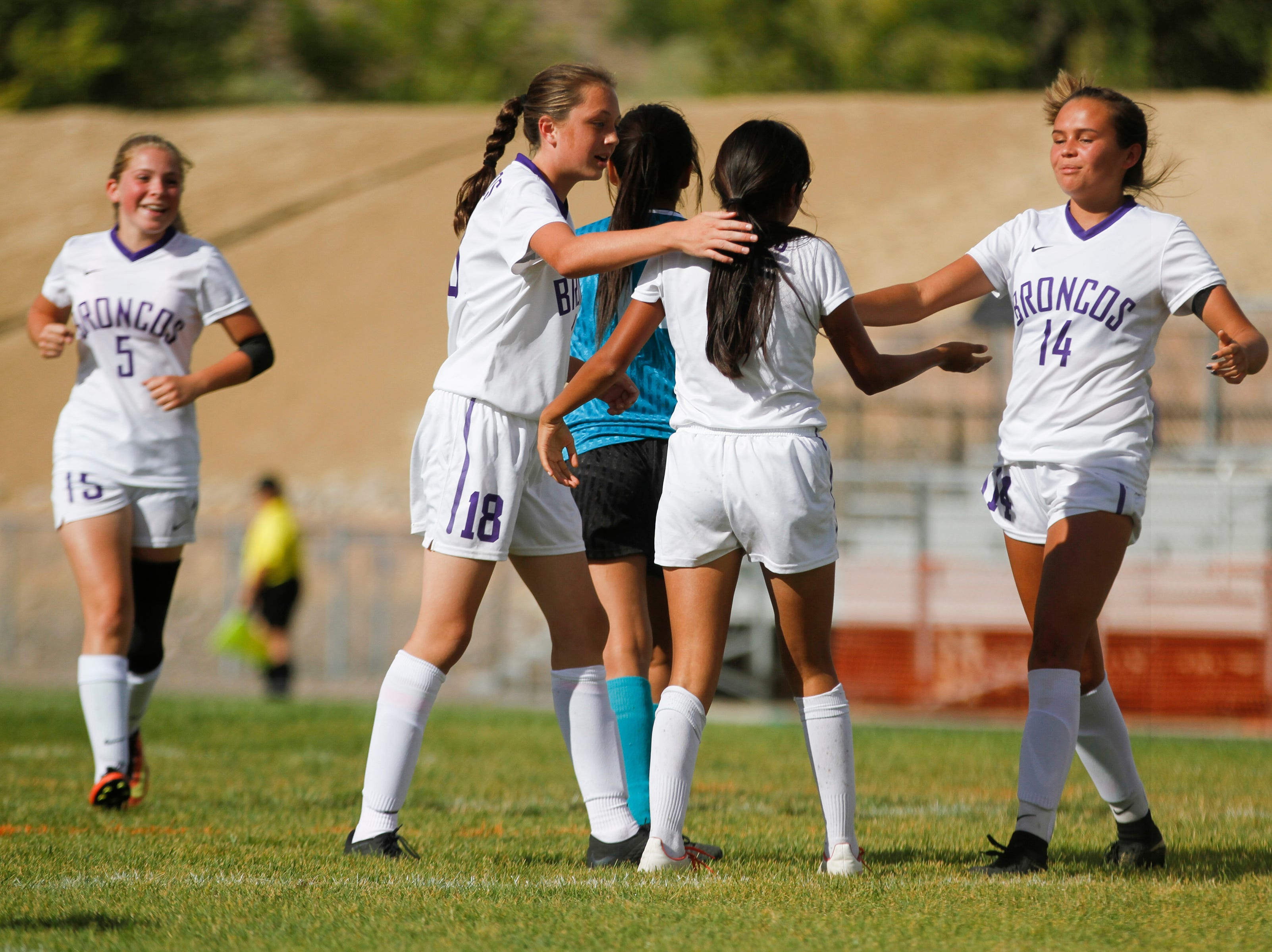 Kirtland Central's Mia Lee, left, Kylie Haws and Hayden Alldredge, right, congratulate teammate Marrissa Henry, second from right, after scoring a goal against Navajo Prep, Thursday, Sept. 6, 2018 at Navajo Prep's Eagle Stadium in Farmington.