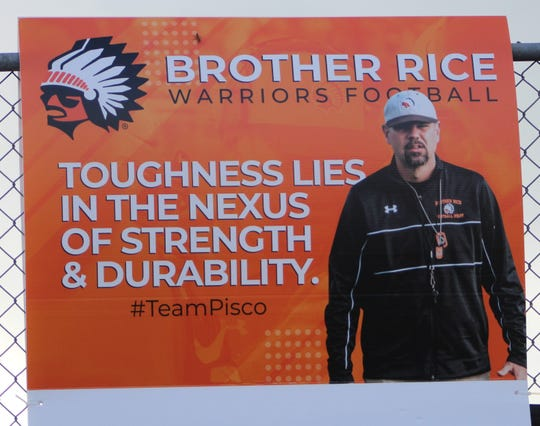 A sign hanging from the fence at Fracassa Field honors Brother Rice's defensive coordinator Greg Piscopink.