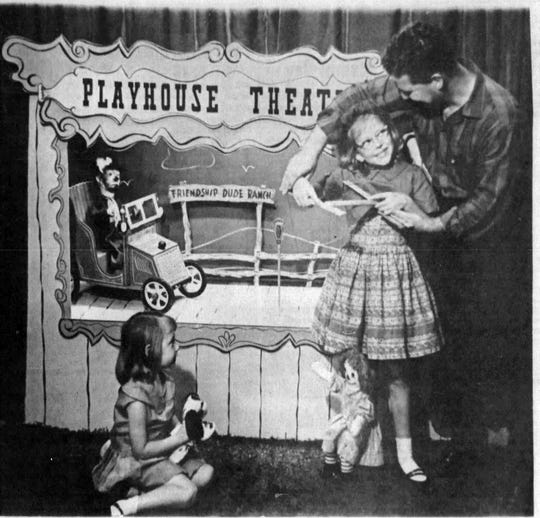 J. A. Allen and daughter Dody practice for their puppet show in the Playhouse Theater while younger daughter Mary Beth looks on , 1964.