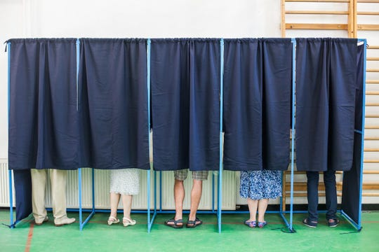 FILE - People voting for candidates in an election