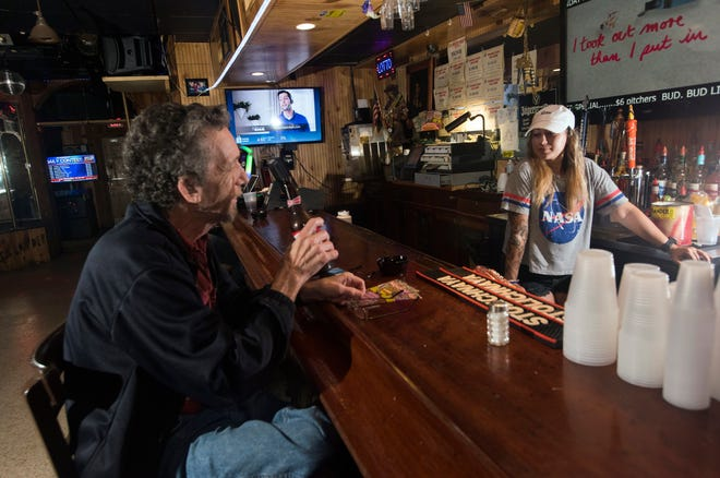 Frank Collier, a regular customer at the Islander Package & Lounge, chats with bartender Tamar Ortiz during his visit to Pensacola Beach on Thursday.