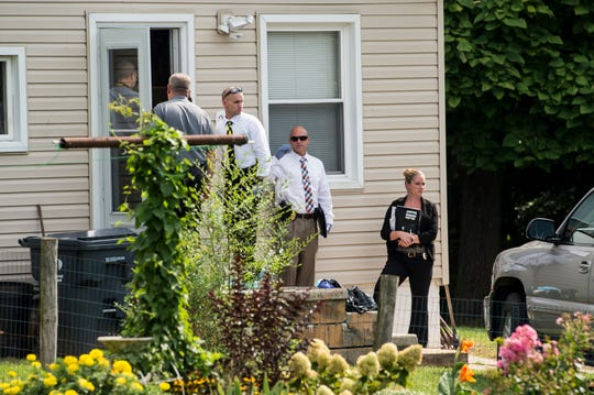 Investigators stand outside the home where a homicide was reported in the 200 block of Middle Street in York Springs on September 6, 2018.