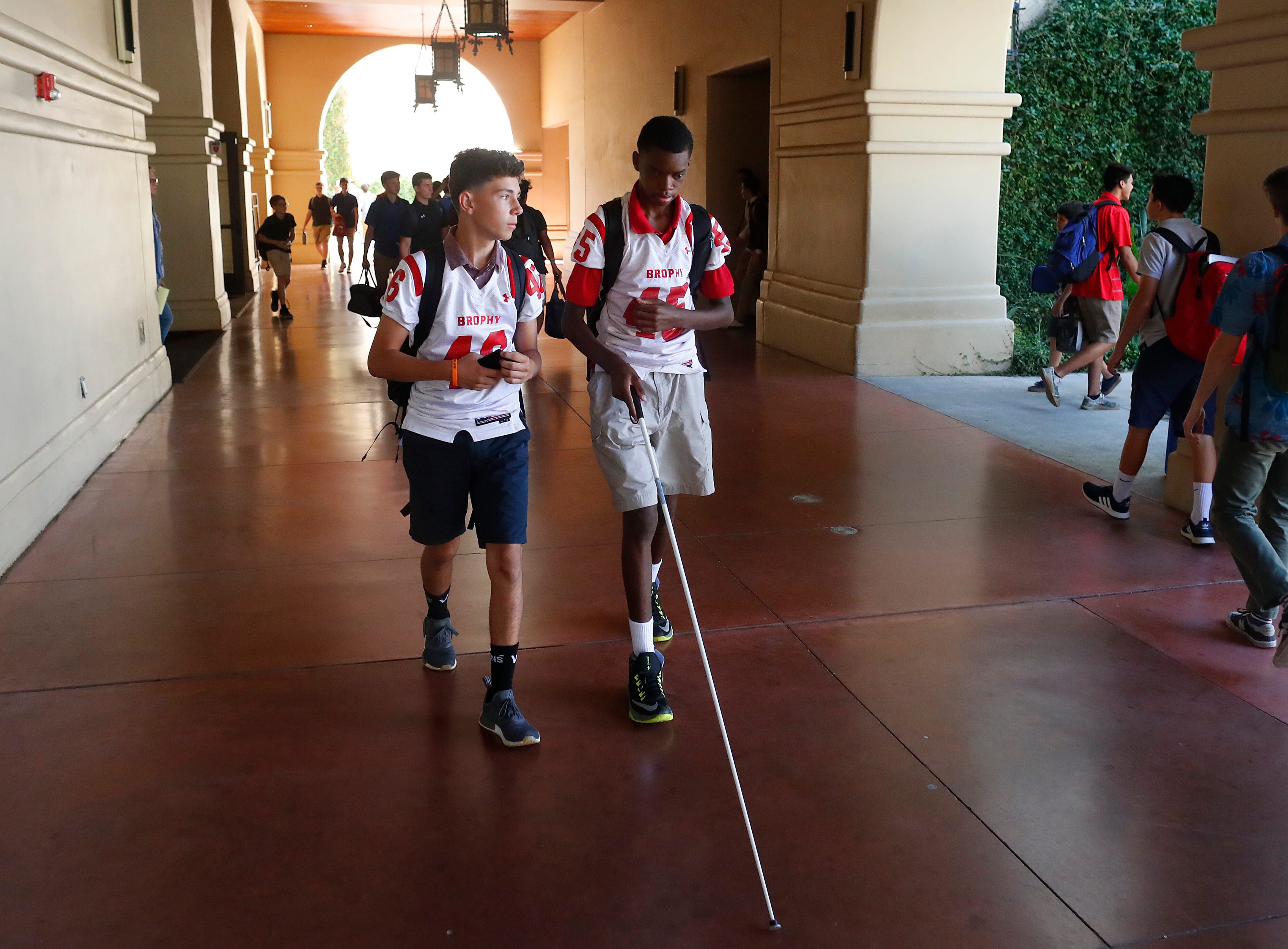 Nick Copeland (L) walks with Adonis Watt between classes at Brophy College Preparatory in Phoenix, Ariz. on Sept. 5, 2018. Freshmen players wear their jerseys to school on game days.