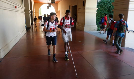 Nick Copeland (L) walks with Adonis Watt between classes at Brophy College Preparatory in Phoenix on Wednesday. Freshman players wear their jerseys to school on game days.