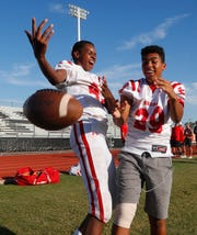 Brophy's Adonis Watt (left) knocks away a pass intended for his teammate Carty Shoen as they have fun before a game against Highland on Aug. 30.