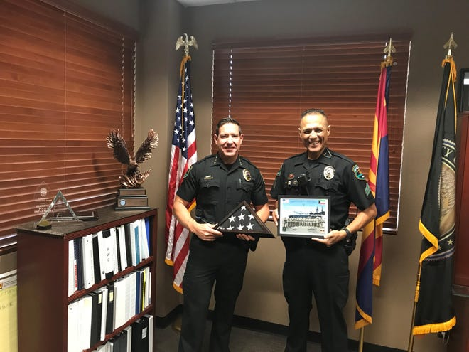"""Glendale Police Chief Rick St. John (left) and Sgt. Patrick Valenzuela (right) pose with a """"thin blue line"""" flag honoring officers who serve."""