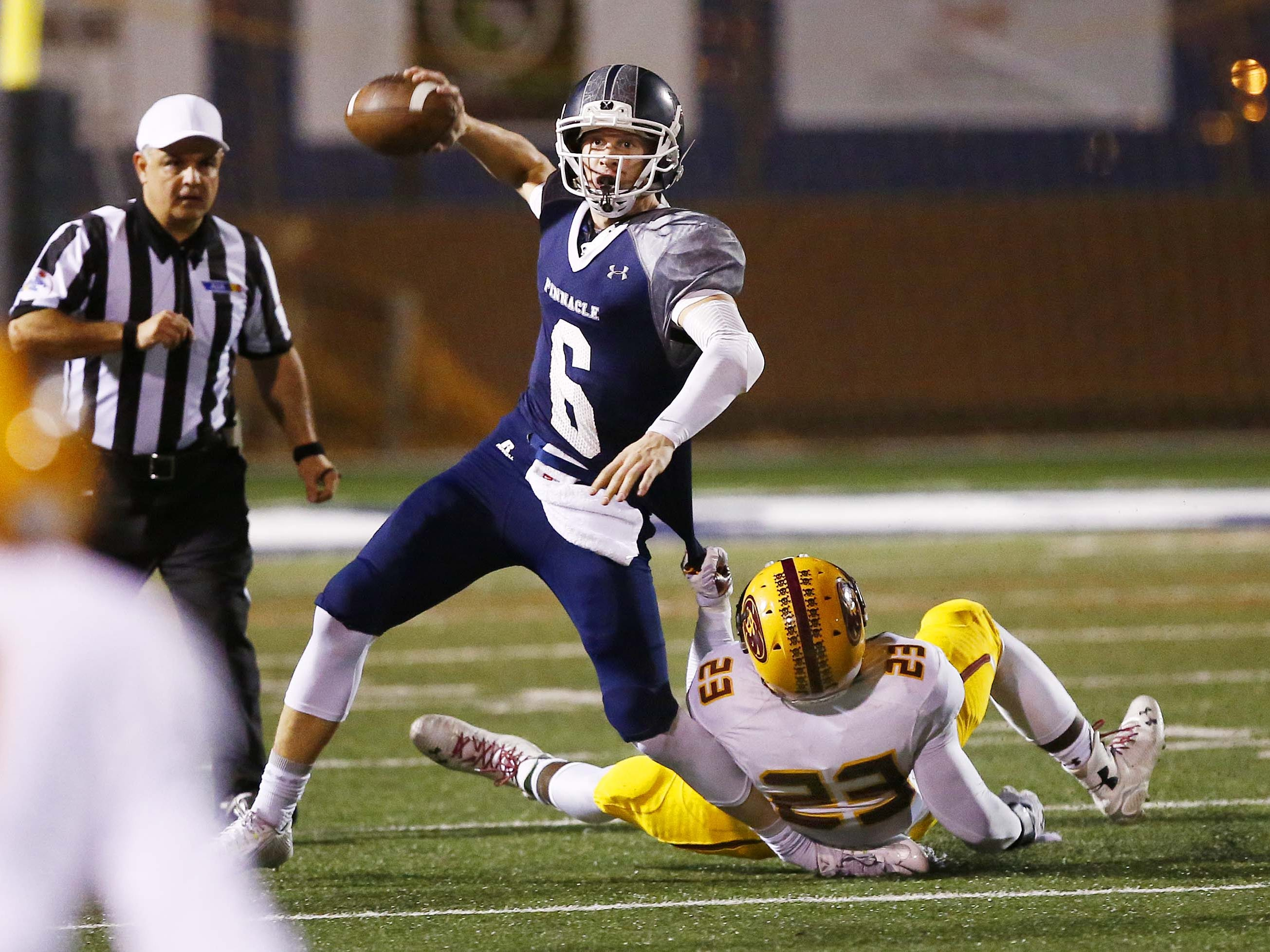 Mountain Pointe's #23 Vavrix Owens tries to tackle Pinnacle quarterback #6 Brian Lewerke in the first half during Division I football quarterfinal action on Friday, Nov. 14, 2014 at Pinnacle High School in Phoenix, AZ.