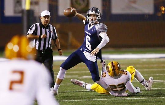 Pinnacle quarterback Brian Lewerke tries to escape a Mountain Pointe tackle in the 2014 playoffs.