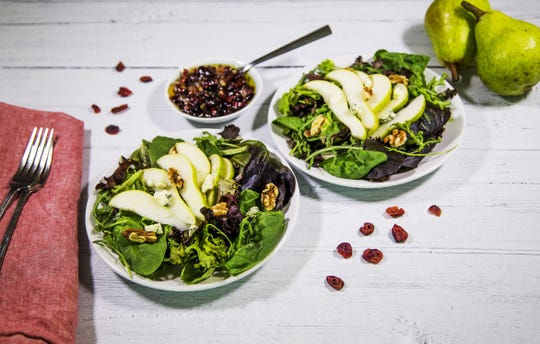 Fall pear salad with walnuts and blue cheese in a cranberry-lemon vinaigrette.