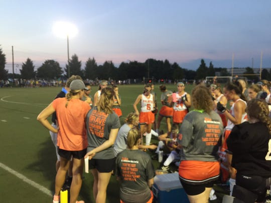 The Palmyra field hockey team discusses strategy at halftime of Wednesday's 0-0 tie with arch rival Lower Dauphin.