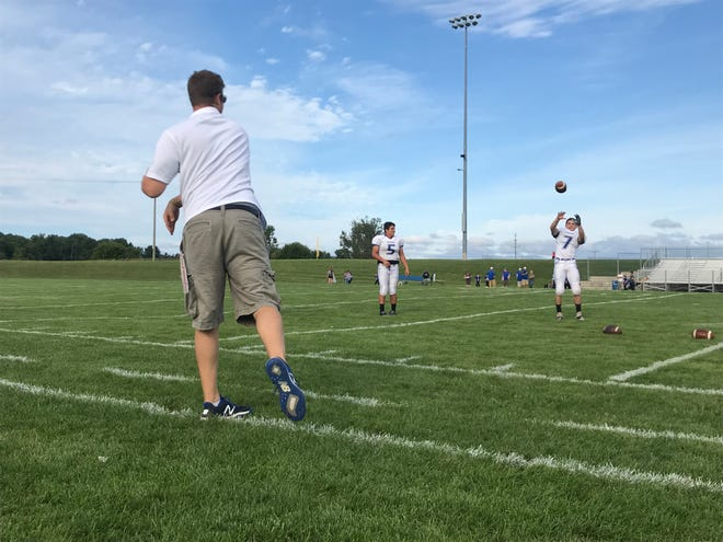 Croswell-Lexington coach Garrett Grundman throws the ball to running back Paul Scaramuzzino while quarterback Joey Johnston looks on.
