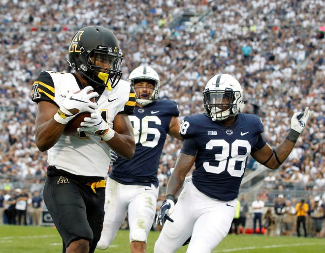 Appalachian State's Malik Williams (14) hauls in touchdown as Penn State's Lamont Wade (38) and Jan Johnson (36) give chase during the second half of an NCAA college football game in State College, Pa., Saturday, Sept. 1, 2018. Penn State won 45-38 in OT. (AP Photo/Chris Knight)