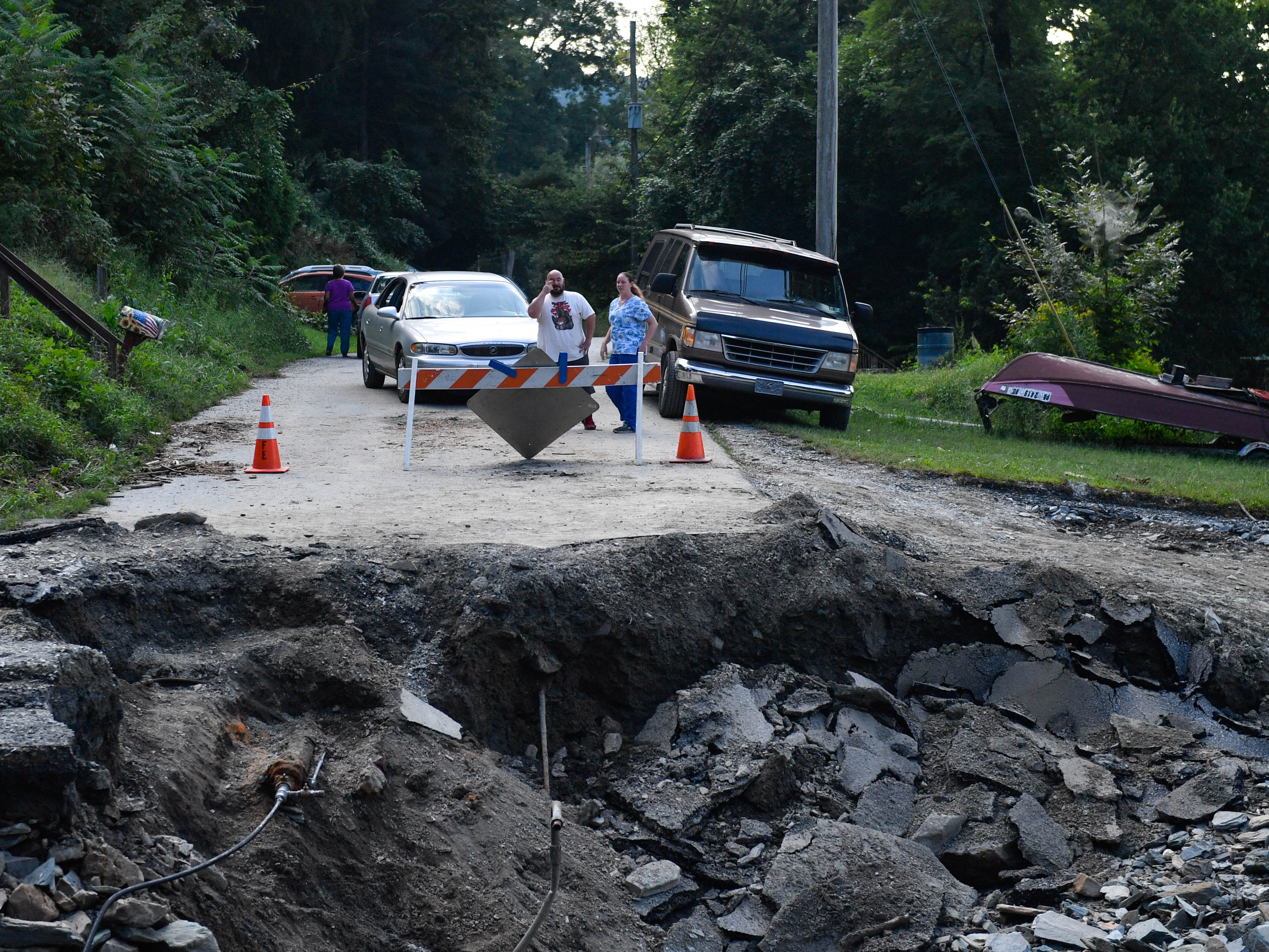 With the bridge gone, residents must take a longer, steeper route out of their neighborhood.