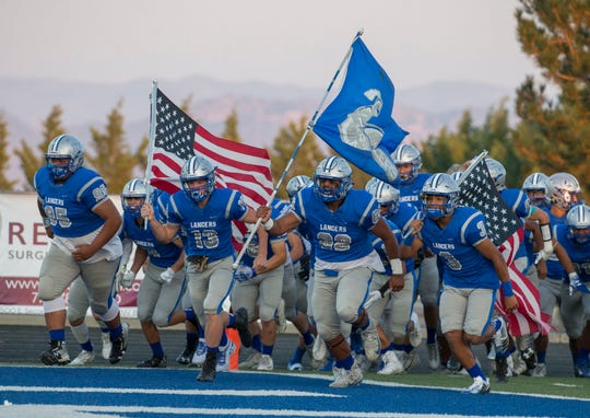 McQueen's Henry Anderson(13), Kirat Dhillon (68) and Jd Kolb(3) lead the Lancers onto the field before thier game agianst Del Campo at McQueen High School on Aug. 31, 2018.