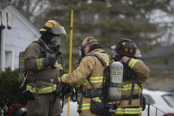 Richmond Fire Department personnel begin removing their breathing equipment after working inside a house fire.