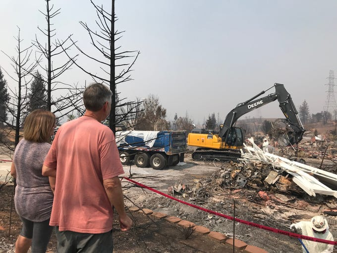 Maureen and  Dan Kissick watch crews clear debris left behind after their home in west Redding was destroyed by the Carr Fire. Their home was one of the first to be serviced by the government's CalRecycle program.