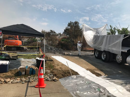 CalRecycle worker places a protective plastic liner in the dump truck that will haul tons of debris left behind after a home burned during the Carr Fire on Spinnaker Drive in Redding. Even the driveway is line with plastic to cut down on contamination.