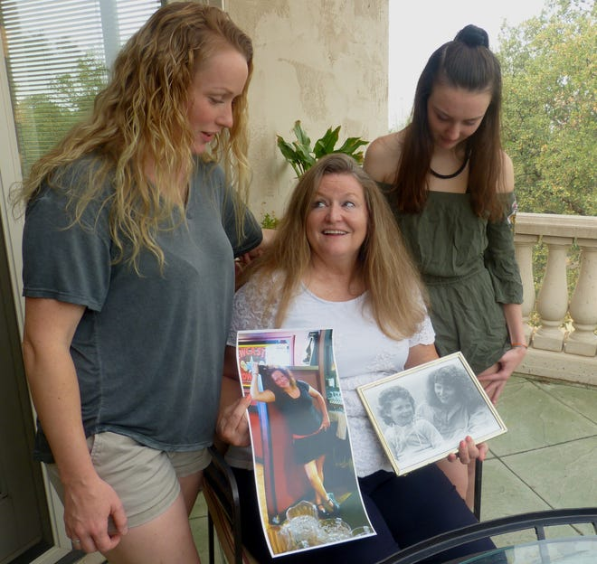 Kelle Clark's mother, Allyn Van Hooser, center, shares photographs with Clark's sister, Cirby Manivong, left, and Clark's 15-year-old daughter, Kelsey Hunter.