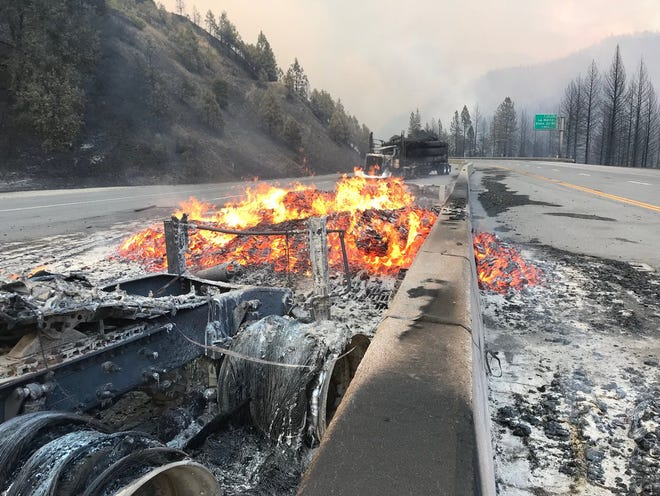 A couple trucks that burned up in the Delta Fire remained burning Wednesday evening, Sept. 5, 2018 on Interstate 5 north of Redding.