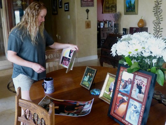Cirby Manivong admires photographs of her sister Thursday at the Redding home of their mother.
