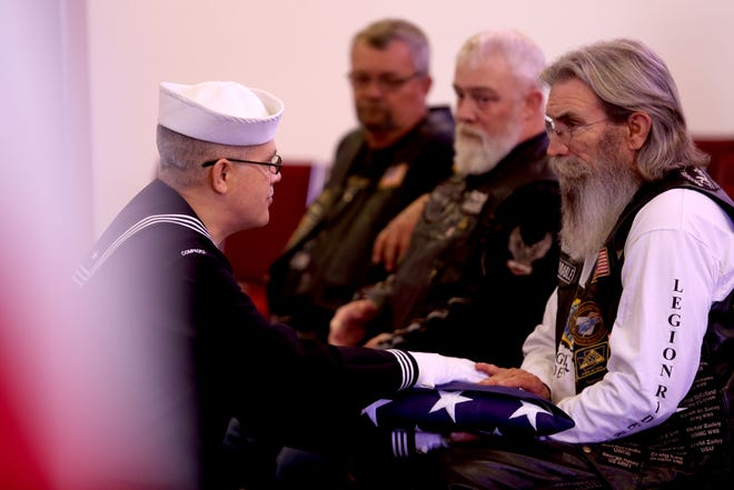 U.S. Navy Intelligence Specialist Harry Thomas presents Blake Lee,  with the veterans flag during a memorial service for Richard Laing, a homeless U.S. Navy veteran, at Weddle Funeral Service in Stayton on Thursday, Sep. 6, 2018.