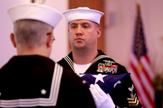 U.S. Navy Master-at-arms Noel Flynn, facing, and Intelligence Specialist Harry Thomas ceremoniously fold the burial flag during a memorial service for Richard Laing, a homeless U.S. Navy veteran, at Weddle Funeral Service in Stayton on Thursday, Sep. 6, 2018.