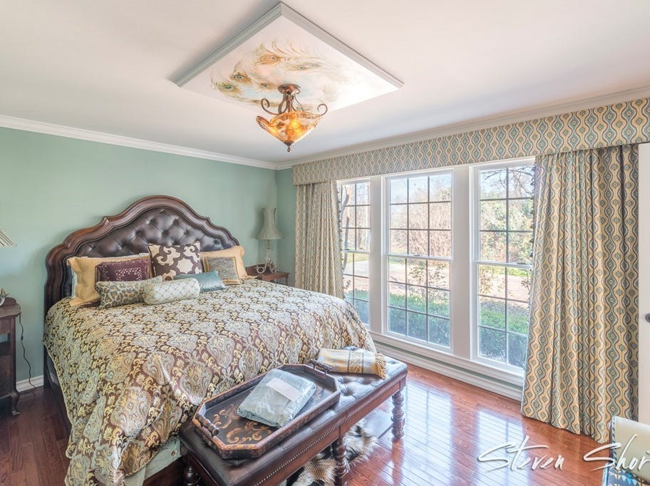 This bedroom is one of four at 1315 S Madison and plays with a light green and leather color palate.