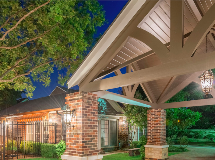 An outdoor night time view of 1315 S Madison St. shows a covered carport and plenty of lighting.