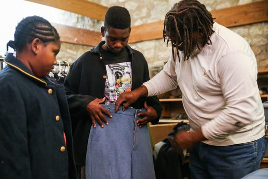 Paul Cook helps his grandson, Jaborien Cook, 14, pic out pants for his Buffalo Soldier uniform as they get ready for Museum Day Saturday Sept. 1, 2018, at Fort Concho.
