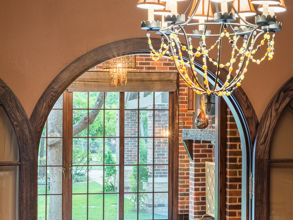 A chandelier, one of many at 1315 S Madison, leads viewers into the den and its French doors.