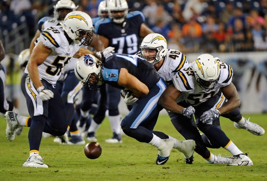 Alex Ellis #49 of the Tennessee Titans fumbles after being hit by Nick Dzubnar #48 and Joshua Perry #53 of the San Diego Chargers during the second half of a game against at Nissan Stadium on August 13, 2016 in Nashville, Tennessee.  Ellis is a graduate of Delmar High School.