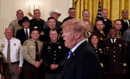 Sheriffs from the United States, including Wicomico County Sheriff Mike Lewis (front row, third from left) listens as President Donald Trump responds to a reporters question during an event in the East Room of the White House in Washington, Wednesday, Sept. 5, 2018.