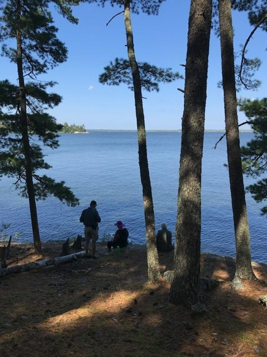 Road Scholars enjoy a picnic lunch at Chief Woodenfrog Point on the shores of Lake Kabetogama.