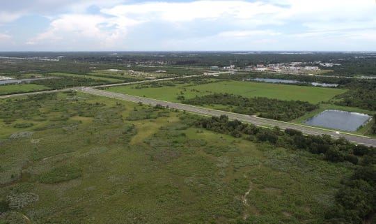 The area for the planned 160-acre Space Coast Town Center west of I-95, bisected by St. Johns Heritage Parkway (center), is seen Thursday, Sept. 6, 2018, in West Melbourne. The mixed-use development would be bounded by U.S. 192 to the north, Simon Road to the west, a Melbourne Tillman Water Control District canal to the south, and Byrd's Western Store and a borrow-pit lake to the east.