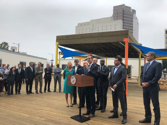 """Mayor Eric Garcetti and City Council members announce the opening of a downtown """"Bridge Home,"""" first of what is planned to be a citywide network of temporary housing sites for homeless people, at a news conference on Wednesday in Los Angeles."""
