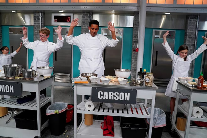 "Ventura resident Carson Peterson, 13, raises his hands after completing a challenge during the taping of the second season of ""Top Chef Jr."" The Cabrillo Middle School student is one of 12 young cooks who earned a spot on the season's debut episode, airing Sept. 8 on Universal Kids."