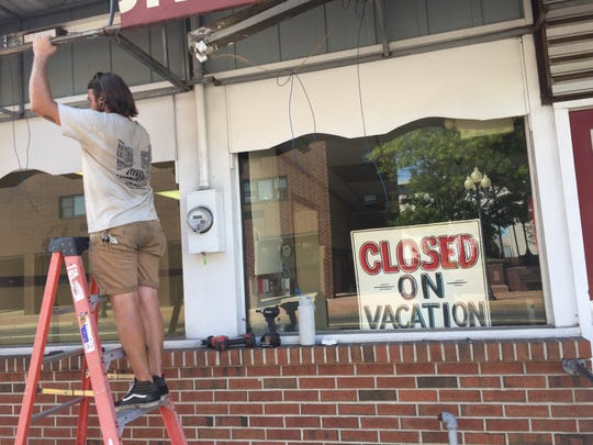 Chris Ball takes his end of the awning outside Jim's Lunch as workers from Lloyd's of Millville prepare to replace the decoration.